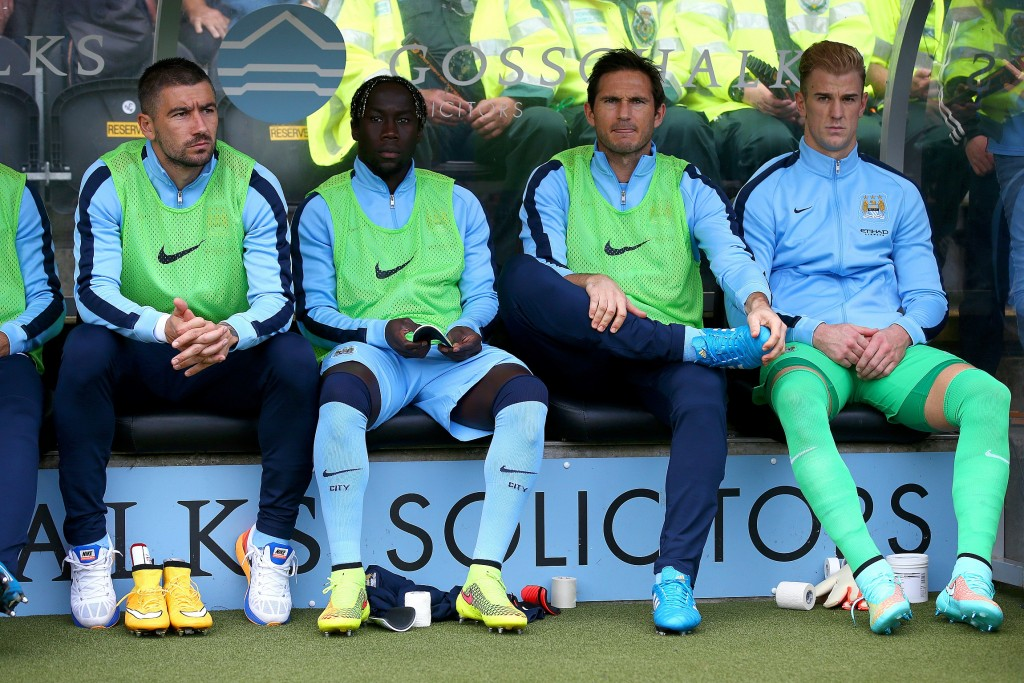 HULL, ENGLAND - SEPTEMBER 27:  Joe Hart of Manchester City sits on the bench next to team-mates Frank Lampard, Bacary Sagna and Aleksandar Kolarov before the Barclays Premier League match between Hull City and Manchester City at KC Stadium on September 27, 2014 in Hull, England.  (Photo by Matthew Lewis/Getty Images)
