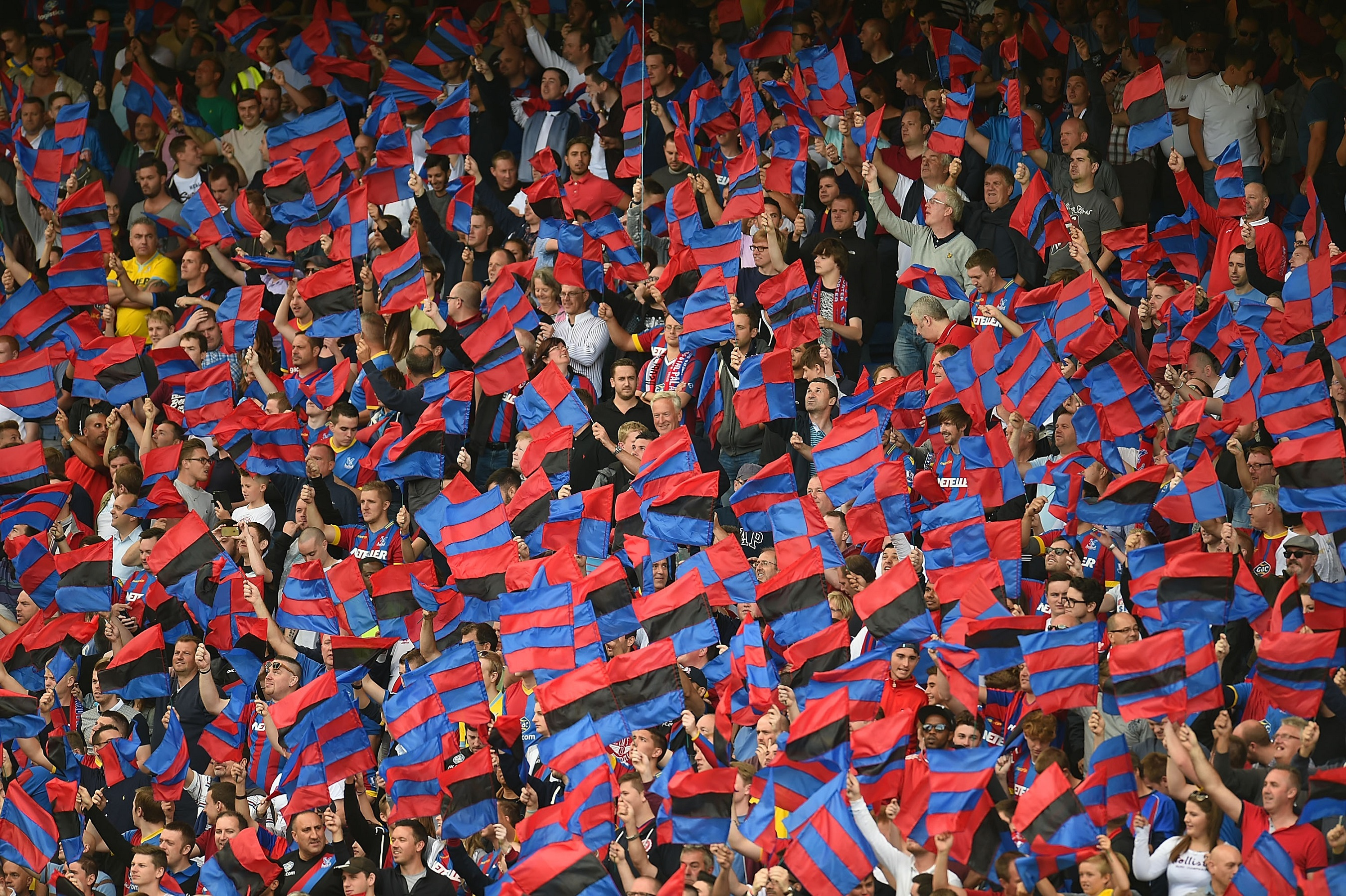 LONDON, ENGLAND - AUGUST 23: Crystal Palace fans wave flags during the Premiere League match between Crystal Palace and West Ham United at Selhurst Park on August 23, 2014 in London, England. (Photo by Tom Dulat/Getty Images)
