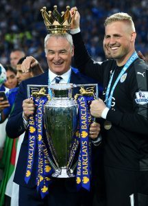 LEICESTER, ENGLAND - MAY 07: Claudio Ranieri poses with the Premier League Trophy while Kasper Schmeichel puts the crown on the head of the manager as players and staffs celebrate the season champions after the Barclays Premier League match between Leicester City and Everton at The King Power Stadium on May 7, 2016 in Leicester, United Kingdom. (Photo by Shaun Botterill/Getty Images)